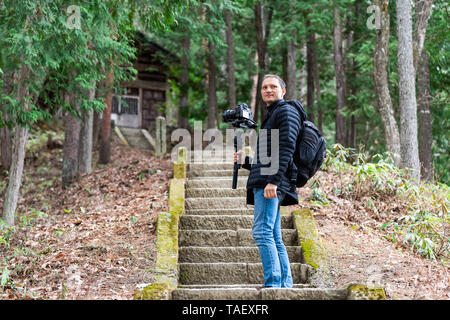 Takayama, Japan wooden house shrine in traditional Hida no Sato old folk village with steps up and young tourist man walking in Gifu prefecture - Stock Photo