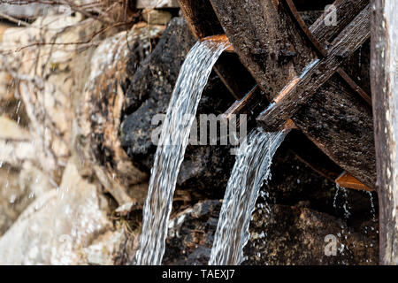 Takayama, Japan traditional wooden house building mill wheel with water running in Hida no Sato old folk village closeup - Stock Photo