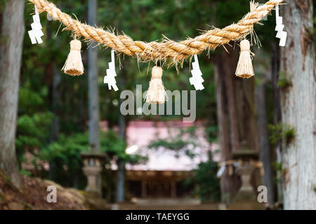Takayama, Japan Higashiyama Shinmei shrine entrance in historical city in Gifu Prefecture torii gate with hanging folded paper on rope - Stock Photo