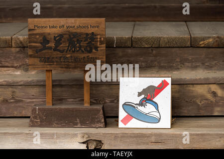 Takayama, Japan - April 9, 2019: Higashiyama Hokkeji temple on walking course in historical city in Gifu Prefecture with funny sign for no shoes and c - Stock Photo