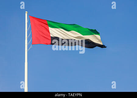 Flag of United Arab Emirates flying in the wind against a blue sky - Stock Photo
