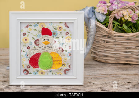 A big chicken with Easter eggs is embroidered and applied. It is located in a white frame. Merry decoration for Easter in front of primroses in the ba - Stock Photo