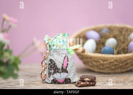 A small bag is filled with jewelry. An Easter bunny was applied. This patchwork stands in front of a nest with Easter eggs. Pink background with copy  - Stock Photo