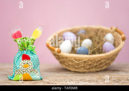A small bag is filled with sweets. A chicken was applied. This patchwork stands in front of a nest with Easter eggs. Pink background with copy space. - Stock Photo