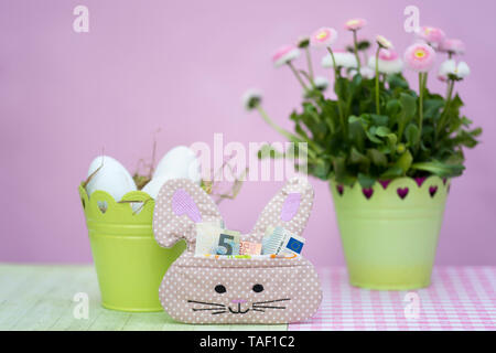 A small bag in the shape of a bunny is filled with money as a gift for Easter. spring flowers Bellis perennis, Easter nest with eggs in green metal po - Stock Photo