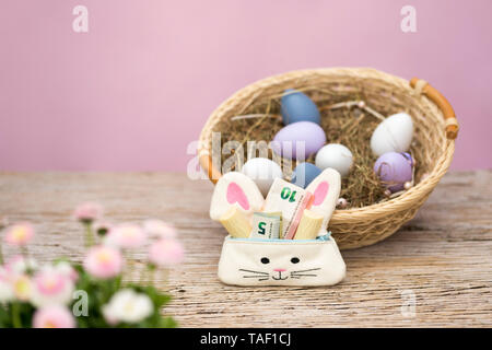 A small bag in the shape of a rabbit is filled with money and sweets as a gift for Easter. In the foreground are spring flowers, in the background is  - Stock Photo