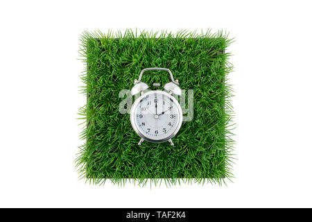 Old style alarm clock on square of green grass field isolated on white background with clipping path - Stock Photo