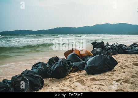 black plastic garbage bags full of trash on the beach. Garbage collection, cleaning of the nature, garbage collection on the beach. - Stock Photo