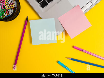 Laptop sticky notes clips container pencils markers colored background - Stock Photo