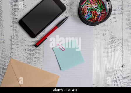 Smartphone paper sheet clips holder pen envelope note wooden background - Stock Photo