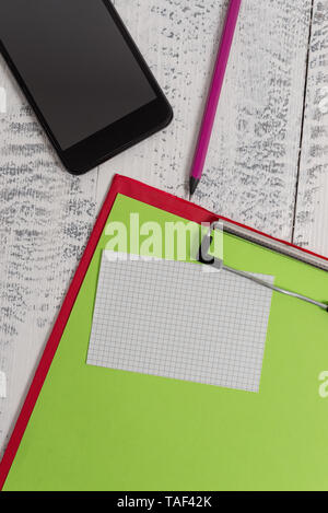 Clipboard sheet pencil smartphone squared sticky note wooden background - Stock Photo