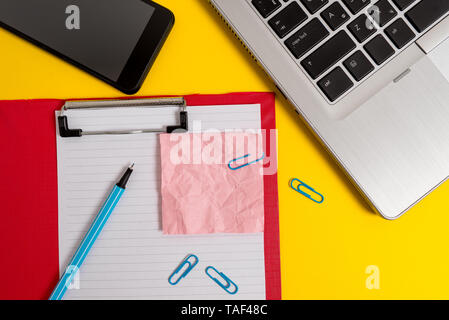 Laptop clipboard sheet clips marker note smartphone colored background - Stock Photo