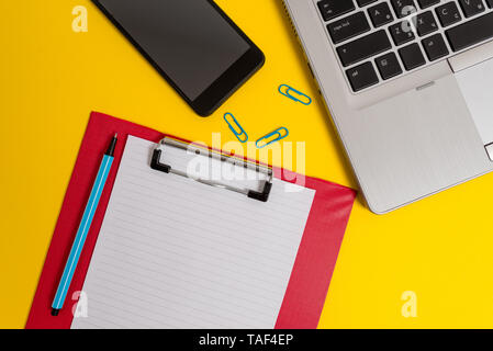 Open laptop clipboard sheet smartphone marker clips colored background - Stock Photo
