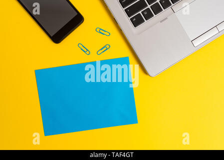 Trendy open laptop smartphone small paper sheet clips colored background - Stock Photo