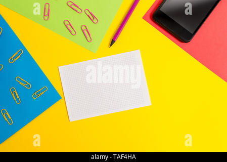 Paper sheets pencil clips smartphone squared notebook colored background - Stock Photo