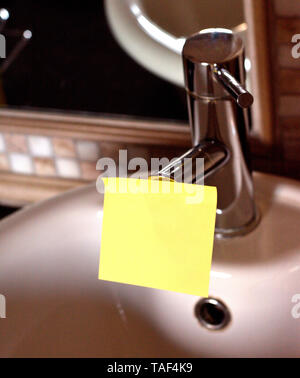 Piece of square paper use to give notation stick to water tap in bathroom - Stock Photo