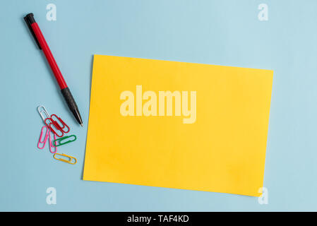 Plain cardboard and writing equipment placed above pastel colour backdrop - Stock Photo