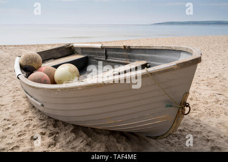 Old fishing boat on Bournemouth beach near Branksome Chine with the sea and Studland in the distance - Stock Photo