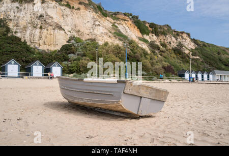 Old fishing rowing boat on Bournemouth beach with cliffs and beach huts in background near Branksome Chine - Stock Photo