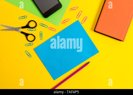 Paper sheets pencil clips smartphone scissors notebook colored background - Stock Photo