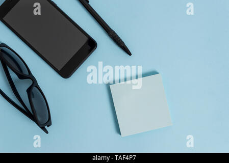 Eyeglasses colored sticky note smartphone cell pen cool pastel background - Stock Photo