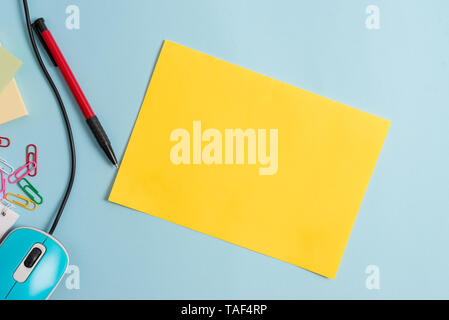 Cardboard and writing equipment with modern gadget above pastel backdrop - Stock Photo