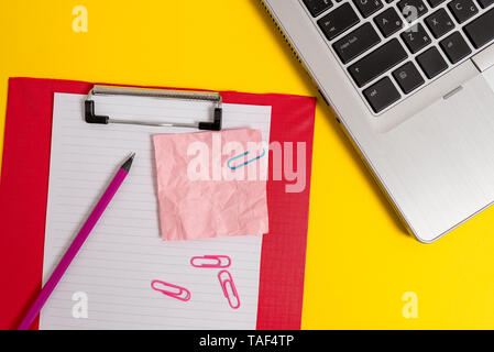 Laptop clipboard paper sheet clips pencil crushed note colored background - Stock Photo