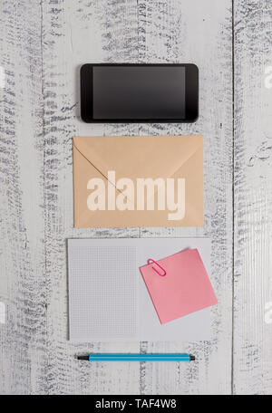 Envelop smartphone notepad note clip marker old wooden vintage background - Stock Photo