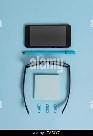 Dark eyeglasses colored sticky note smartphone pen clips pastel background - Stock Photo