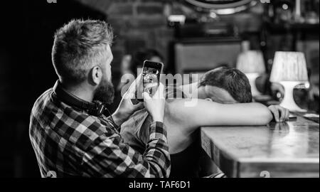 Man drunk fall asleep and guy with smartphone. Hipster taking photo drunk friend. Drunk friends in bar. Fall asleep at bar counter. Take photo to remember party. Hipster making fun of drunk friend. - Stock Photo