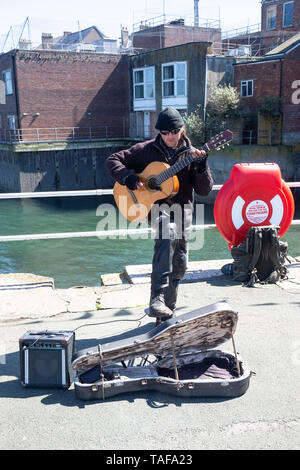 Guitar playing busker dressed against the elements on the Prince of Wales pier in Falmouth, Cornwall U.K. - Stock Photo