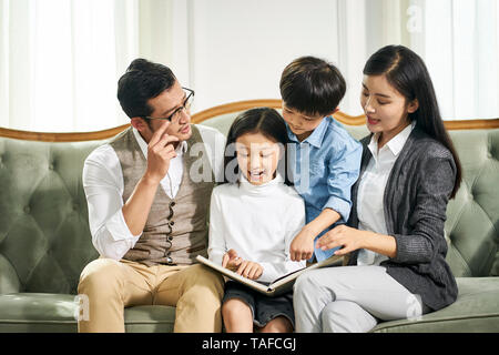 young asian father and mother and two children sitting on couch reading book together in family living room at home - Stock Photo
