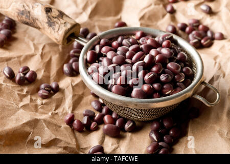 Raw, uncooked, dried adzuki (red mung) beans in small sieve on brown packing paper background with selective focus - Stock Photo