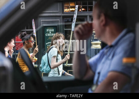 Westminster, London, UK - 24th May 2019.  A taxi driver, stuck in traffic due to the march, watches a young protester walk past from his cab. Thousands of young people, some with their parents, once again take to the streets of Westminster to protest against the impact of climate change and environmental problems, as well as inactivity of governments. Protest sites include Parliament Square, Whitehall and Trafalgar Square in London, and many other cities in the UK and globally. Credit: Imageplotter/Alamy Live News - Stock Photo