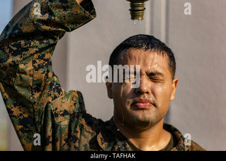 Iwakuni, Japan. 23rd May, 2019. U.S. Marine Corps Lance Cpl. Cesar Ramirez pours a canteen of water on his head to cool off after a conditioning hike on a hot day at Marine Corps Air Station May 23, 2019 in Iwakuni, Japan. Credit: Planetpix/Alamy Live News - Stock Photo