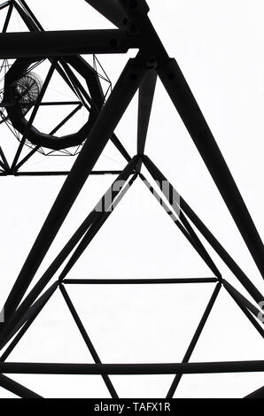Amazing view of the steel construction of the Tetrahedron in Bottrop, Germany taken from below against white sky. A walkable steel structure in form of a tetrahedron taken on a black and white photo. - Stock Photo