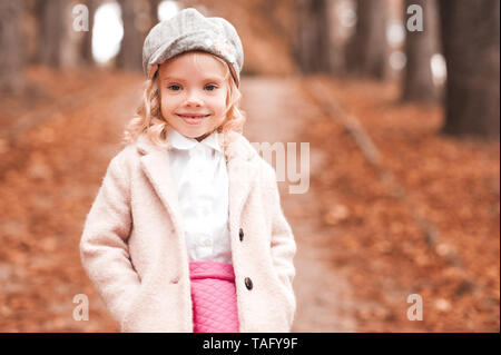 Smiling kid girl 3-4 year old wearing trendy winter jacket and cap outdoors. Walking in park. Autumn season. Childhood. - Stock Photo