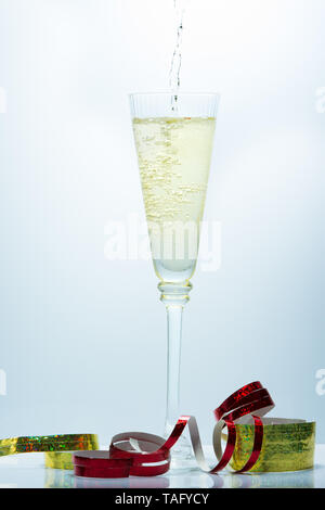 Pouring of Champagne on a fancy glass against a blue background - Stock Photo