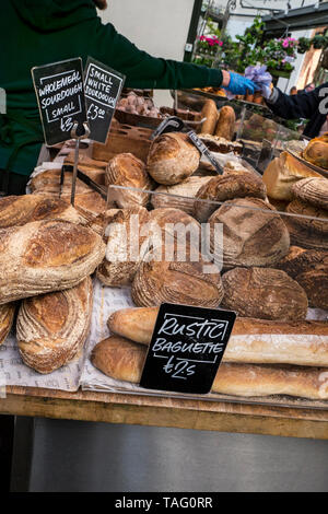 Rustic authentic Baguette and Sourdough breads at Borough Market Bakery. Speciality bread Borough Market Bakery 'Bread Ahead' stall inside with variety of attractive hand made artisan breads on display for sale. Artisan speciality bakery stall at Borough Market Southwark London UK - Stock Photo