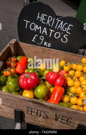 Heritage Tomatoes Teds Veg home grown display at Borough Market with heart shaped blackboard price tag An heirloom tomato (also called heritage tomato in the UK) is an open-pollinated (non-hybrid) heirloom cultivar of tomato. According to tomato experts, heirloom tomatoes can be classified into four categories: family heirlooms, commercial heirlooms, mystery heirlooms, and created heirlooms. They usually have a shorter shelf life and less disease resistance than hybrids bred to resist against specific diseases. They are grown for a variety of reasons, for food, historical interest & taste - Stock Photo