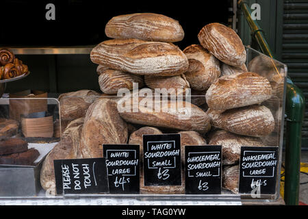 Speciality bread Borough Market Bakery 'Bread Ahead' stall with variety of attractive hand made artisan breads on display for sale with white Sourdough bread displayed in foreground. Artisan speciality bakery stall at Borough Market Southwark London UK - Stock Photo
