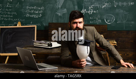 Bearded man hold bulb in classroom. Scientist hipster with lightbulb on chalkboard. Businessman in suit sit at school desk. Teacher with long beard on - Stock Photo