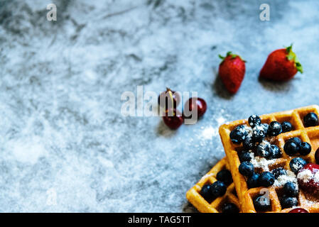 Close-up of a waffle with blueberries and strawberries with delicious aspect, isolated on abstract background with copy space for text. - Stock Photo