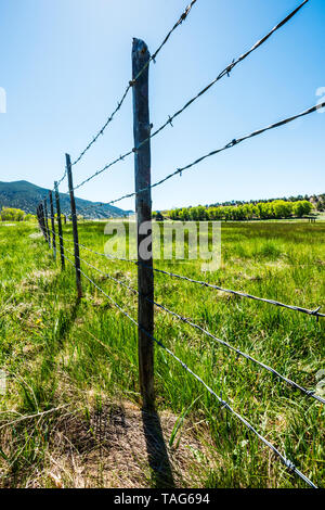 Close-up of barbed wire fence & wooden fence posts against clear blue sky; ranch in Central Colorado; USA - Stock Photo