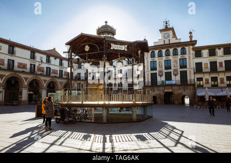 Tudela, Navarre, Spain - February, 13th, 2019 :  Two women stand by the Bandstand at the 17th century Plaza Nueva or Plaza de los Fueros square, with  - Stock Photo