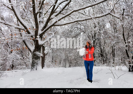 A young beautiful woman in a bright coral-colored jacket and blue jeans walks in the winter through the snow-covered fairy-tale forest near a branchy, - Stock Photo