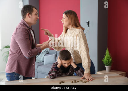 Sad little boy with coins and his quarreling parents at home. Concept of child support - Stock Photo