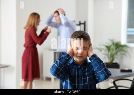 Sad little boy with his quarreling parents in lawyer's office. Concept of child support - Stock Photo