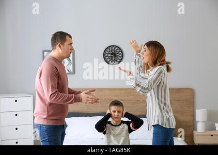 Sad little boy covering ears while his parents arguing at home - Stock Photo