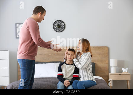 Sad little boy with his quarreling parents at home - Stock Photo
